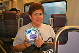 Image of Metrolink Los Angeles rider holding Moo: The Liberty Cow plush animal